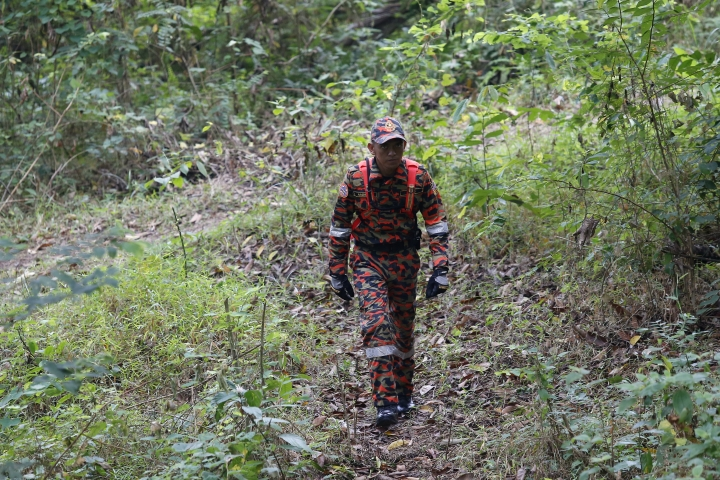 A member of rescue team conducts a search and rescue operation for a missing British girl at a forest in Seremban, Negeri Sembilan, Malaysia, Friday, Aug. 9, 2019. Police in Malaysia said on Thursday that they are using voice recordings conducted with the family of the 15-year old missing girl from London, in order to find her. (AP Photo/Lai Seng Sin)