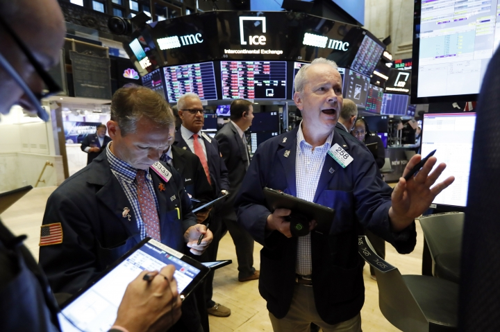 James Riley, right, works with fellow traders on the floor of the New York Stock Exchange, Friday, Aug. 9, 2019. Stocks moved broadly lower in early trading On Wall Street Friday as investors again retreated to safer holdings in a market racked by fear and anxiety over trade disputes. (AP Photo/Richard Drew)
