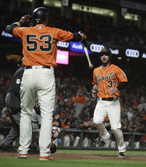 San Francisco Giants' Joey Rickard, right, scores as Austin Slater (53) waits to congratulate him during the sixth inning of the team's baseball game against the Philadelphia Phillies on Friday, Aug. 9, 2019, in San Francisco. (AP Photo/Ben Margot)
