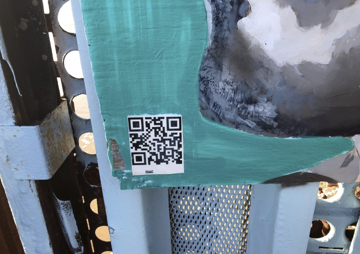 A barcode that will let a visitor hear the story of the person depicted on a personal device, is seen on a new mural on the Mexican side of a border wall in Tijuana, Mexico, Friday, Aug. 9, 2019. The mural shows faces of people deported from the U.S., with barcodes that activate first-person narratives on visitors' phones. Lizbeth De La Cruz Santana conceived the interactive mural in Tijuana as part of doctoral dissertation at the University of California, Davis. (AP Photo/Elliot Spagat)