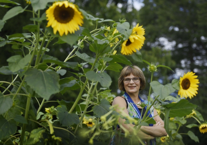 In this Thursday August 8, 2019 photo, Karen Breda poses for a photograph in a garden in West Hartford, Conn. Breda attended Woodstock to see a music concert that included the Who, Jimi Hendrix, Jefferson Airplane and Crosby, Stills, Nash & Young in the lineup. (AP Photo/Jessica Hill)