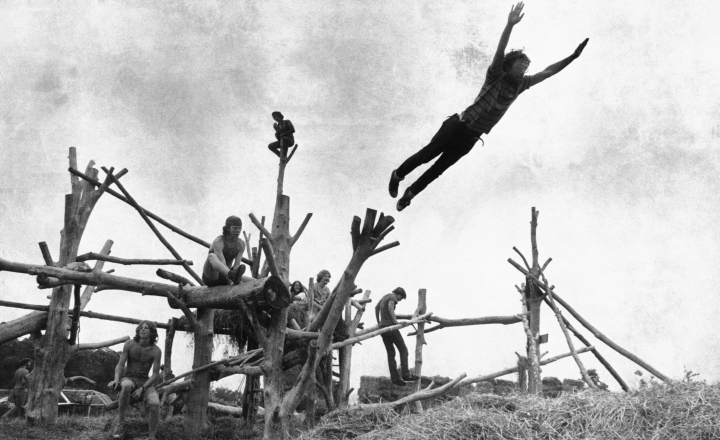 "In this Aug. 15, 1969 file photo rock music fans sit on a tree sculpture as one leaps mid-air onto a pile of hay during the Woodstock Music and Art Festival held in Bethel, N.Y. To some Americans, the pivotal festival of ""peace and music"" 50 years ago was an inspiring moment of countercultural community and youthful freethinking. To others, it was an outrageous display of indulgence, moral decay and insouciance in a time of war. To still others, it was just a world apart from theirs. (AP File Photo, File)"