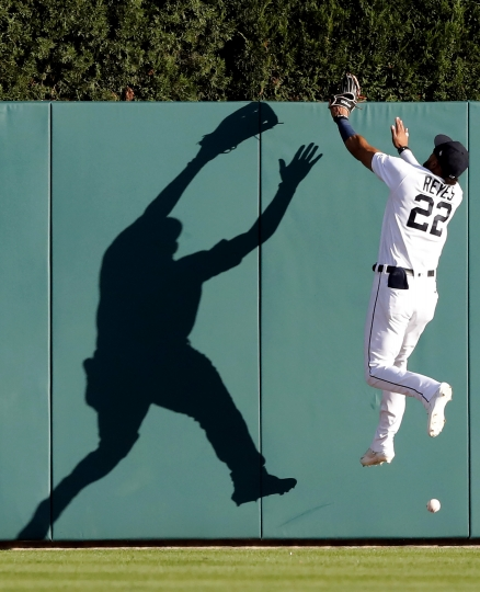 Detroit Tigers center fielder Victor Reyes misplays a ball hit by Kansas City Royals' Whit Merrifield for an inside-the-park home run during the first inning of a baseball game, Friday, Aug. 9, 2019, in Detroit. (AP Photo/Carlos Osorio)