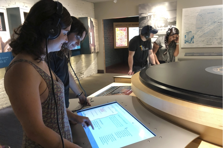 In this June 26, 2019 photo, Katie Dickerson and Kyrra Engle listening to an early country music recording at the Birthplace of Country Music Museum in Bristol, Va. Ten medical students were on a tour of the city organized by a medical school with the aim of luring them to practice in rural communities facing health care shortages after graduation. (AP Photo/Sudhin Thanawala)