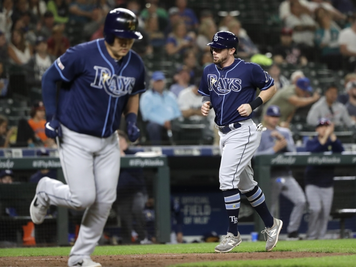Tampa Bay Rays' Eric Sogard, right, heads in to score as Ji-Man Choi heads to first base on a bases-loaded walk in the ninth inning of the team's baseball game against the Seattle Mariners on Friday, Aug. 9, 2019, in Seattle. (AP Photo/Elaine Thompson)