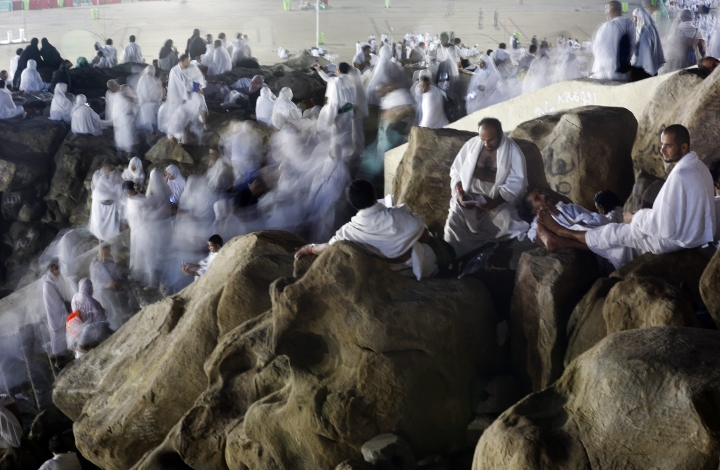 In this picture taken with low shutter speed, Muslim pilgrims make their way up on a rocky hill known as Mountain of Mercy, on the Plain of Arafat, during the annual hajj pilgrimage, ahead of sunrise near the holy city of Mecca, Saudi Arabia, Saturday, Aug. 10, 2019. More than 2 million pilgrims were gathered in the holy city of Mecca in Saudi Arabia on Friday to perform initial rites of the hajj, an Islamic pilgrimage that takes the faithful along a path traversed by the Prophet Muhammad some 1,400 years ago. (AP Photo/Amr Nabil)