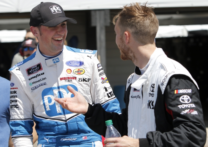 Austin Cindric, left, and Jack Hawksworth talk in the garage after qualifying for the NASCAR Xfinity Series auto race, Saturday, Aug. 10, 2019, at Mid-Ohio Sports Car Course in Lexington, Ohio. Cindric won the pole award for the race. (AP Photo/Tom E. Puskar)