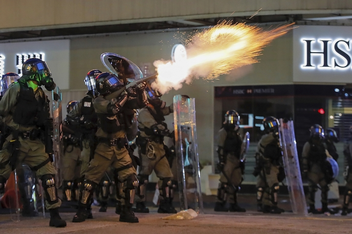 Riot police fire tear gas during the anti-extradition bill protest in Hong Kong, Sunday, Aug. 11, 2019. Police fired tear gas late Sunday afternoon to try to disperse a demonstration in Hong Kong as protesters took over streets in two parts of the Asian financial capital, blocking traffic and setting up another night of likely showdowns with riot police. (AP Photo/Kin Cheung)