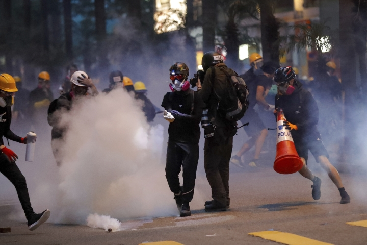 Protesters use traffic cones to cover the tear gas canisters fired by riot policemen during the anti-extradition bill protest in Hong Kong, Sunday, Aug. 11, 2019. Police fired tear gas late Sunday afternoon to try to disperse a demonstration in Hong Kong as protesters took over streets in two parts of the Asian financial capital, blocking traffic and setting up another night of likely showdowns with riot police. (AP Photo/Vincent Thian)