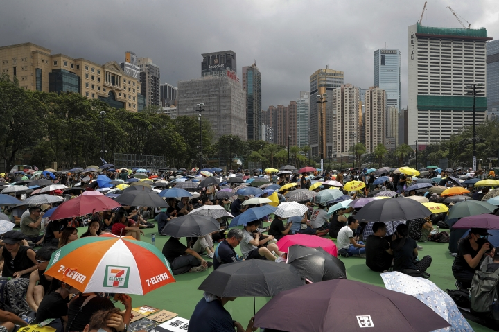 People holding umbrellas gather at Victoria Park to take part in an anti-extradition bill protest in Hong Kong, Sunday, Aug. 11, 2019. Protesters have begun gathering at the park in central Hong Kong for another day of demonstrations that have generally started peacefully but often ended in violent clashes with police. (AP Photo/Vincent Thian)