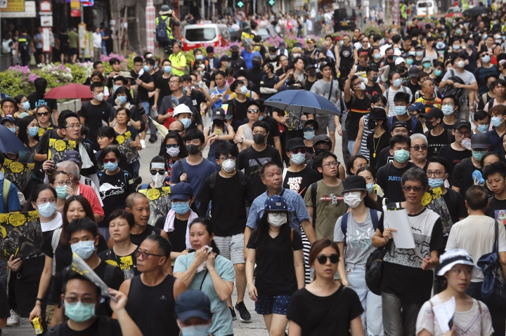 Protesters and residents take part in the anti-extradition bill protest march at Shum Shui Po in Hong Kong, Sunday, Aug. 11, 2019. Separate protests were being held in two parts of Hong Kong on Sunday in a continuing series of demonstrations that have generally started peacefully but often ended in violent clashes with police. (AP Photo/Kin Cheung)