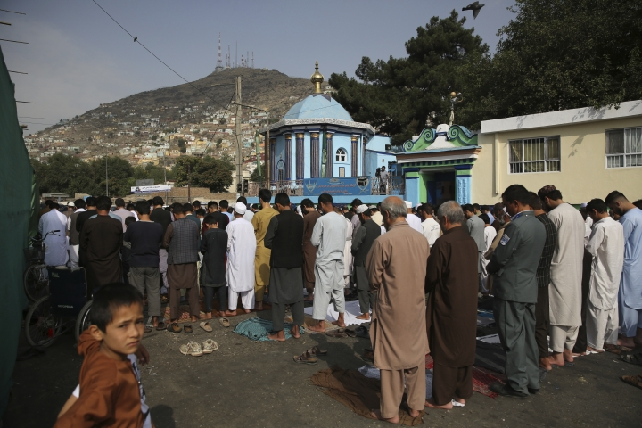 Afghan Muslims offer Eid al-Adha prayers in Kabul, Afghanistan, Sunday, Aug. 11, 2019. Muslim people in the country celebrate Eid al-Adha, or the Feast of the Sacrifice by slaughtering sheep, goats and cows whose meat will later be distributed to the poor.(AP Photo/Rafiq Maqbool)