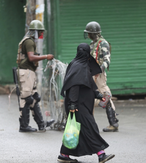 A Kashmiri woman walks past Indian paramilitary soldiers closing off a street with barbwire in Srinagar, Indian controlled Kashmir, Saturday, Aug. 10, 2019. Authorities enforcing a strict curfew in Indian-administered Kashmir will bring in trucks of essential supplies for an Islamic festival next week, as the divided Himalayan region remained in a lockdown following India's decision to strip it of its constitutional autonomy. The indefinite 24-hour curfew was briefly eased on Friday for weekly Muslim prayers in some parts of Srinagar, the region's main city, but thousands of residents are still forced to stay indoors with shops and most health clinics closed. All communications and the internet remain cut off. (AP Photo/Mukhtar Khan)