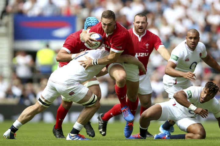 Wales' George North runs with the ball and is tackled by England's Ellis Genge during their International rugby match at Twickenham Stadium in London, Sunday Aug. 11, 2019. (Nigel French/PA via AP)