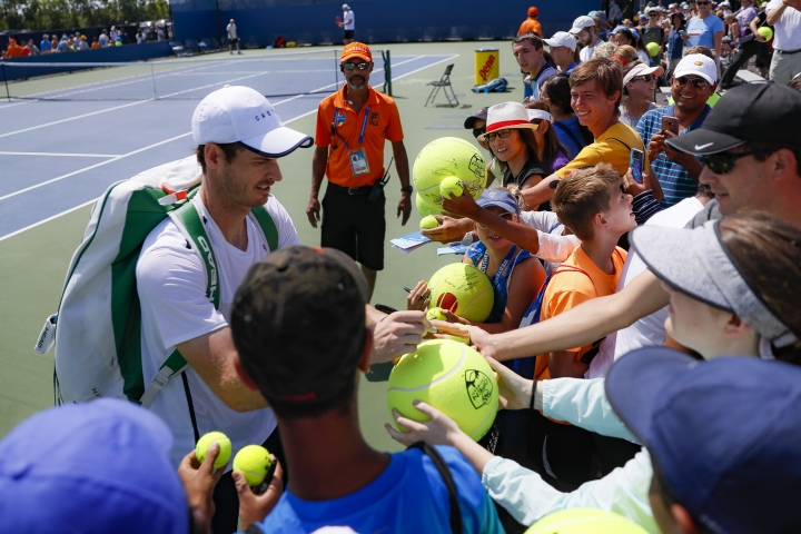 Andy Murray, left, of Britain, signs autographs after practicing at the Western & Southern Open tennis tournament, Sunday, Sunday, Aug. 11, 2019, in Mason, Ohio. (AP Photo/John Minchillo)