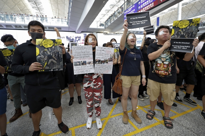 Protesters wear eyepatch during a protest at the arrival hall of the Hong Kong International Airport in Hong Kong, Monday, Aug. 12, 2019. It is reported that police shot a woman in the eye with a projectile Sunday night during confrontations between protesters and police. (AP Photo/Vincent Thian)