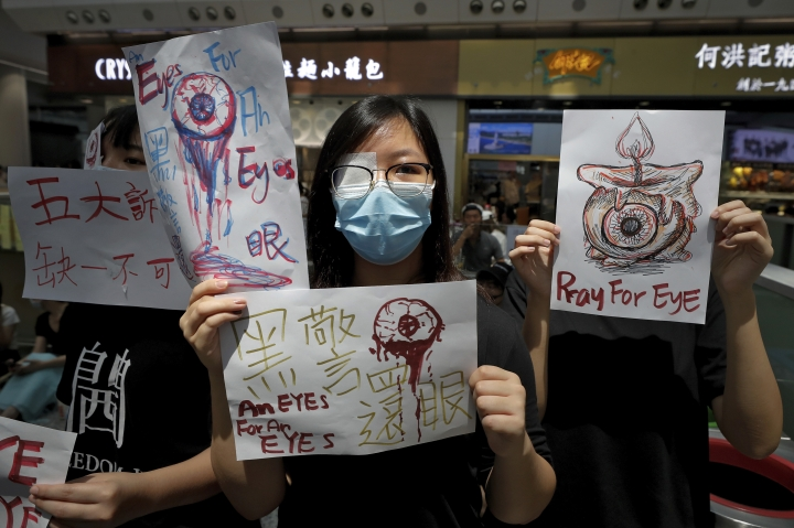 """People hold signs which read """" Black Police, Return eye,"""" bottom center, during a protest at the arrival hall of the Hong Kong International airport in Hong Kong, Monday, Aug. 12, 2019. It is reported that police shot a woman in the eye with a projectile Sunday night during confrontations between protesters and police. (AP Photo/Vincent Thian)"""