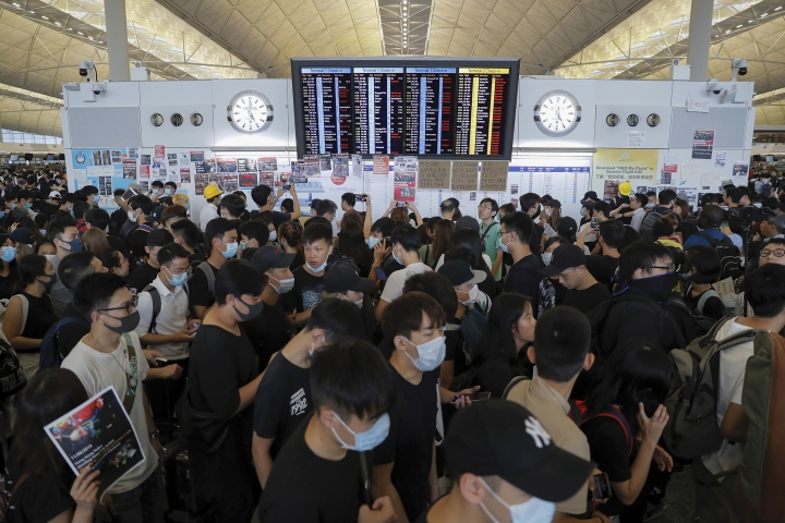 Protesters gather near a flights information board during a protest at the Hong Kong International Airport, Monday, Aug. 12, 2019. One of the world's busiest airports canceled all flights after thousands of Hong Kong pro-democracy protesters crowded into the main terminal Monday afternoon. (AP Photo/Kin Cheung)