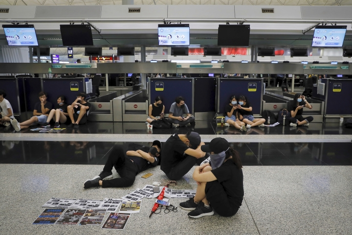 Protesters gather at the closed check-in counters at the Hong Kong International Airport, Monday, Aug. 12, 2019. One of the world's busiest airports canceled all flights after thousands of Hong Kong pro-democracy protesters crowded into the main terminal Monday afternoon. (AP Photo/Kin Cheung)