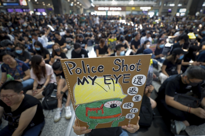 A protester displays a placard during a sit-in protest at the arrival hall of the Hong Kong International Airport in Hong Kong, Monday, Aug. 12, 2019. It is reported that police shot a woman in the eye with a projectile Sunday night during confrontations between protesters and police. (AP Photo/Vincent Thian)