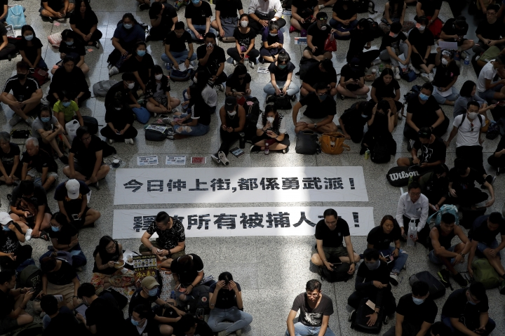 "Protesters surround banners that read: ""Those charge to the street on today is brave!,"" top, and ""Release all the detainees!"" during a sit-in rally at the arrival hall of the Hong Kong International airport, Monday, Aug. 12, 2019. Hong Kong police showed off water cannons Monday as pro-democracy street protests stretched into their 10th week with no sign of either side backing down. (AP Photo/Vincent Thian)"