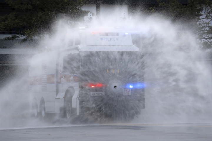 An anti-riot vehicle equipped with water cannon shows its water spraying skill during a demonstration at the Police Tactical Unit Headquarters in Hong Kong, Monday, Aug. 12, 2019. Hong Kong police showed off water cannons during the demonstration of specially equipped armored cars came after another weekend of protests at Hong Kong's bustling international airport and on the streets of one of the city's main shopping districts. (AP Photo/Kin Cheung)