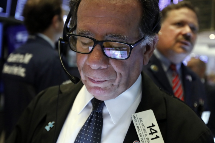 The screen of handheld device of trader Sal Suarino is reflected in his glasses as he works on the floor of the New York Stock Exchange, Tuesday, Aug. 13, 2019. Stocks shot higher on Wall Street after the U.S. government announced it was delaying the implementation of tariffs on certain goods imported from China. (AP Photo/Richard Drew)