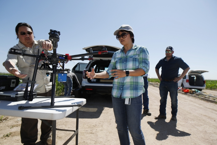 In this Thursday, July 11, 2019, photograph, United States Department of Agriculture Kevin Yemoto, left, an engineering technician, joins Huihui Zhang in setting up a drone for flight over a research farm northeast of Greeley, Colo. as Kendall DeJonge, also of the USDA, looks on. Researchers are using drones carrying imaging cameras over the fields in conjunction with stationary sensors connected to the internet to chart the growth of crops in an effort to integrate new technology into the age-old skill of farming. (AP Photo/David Zalubowski)