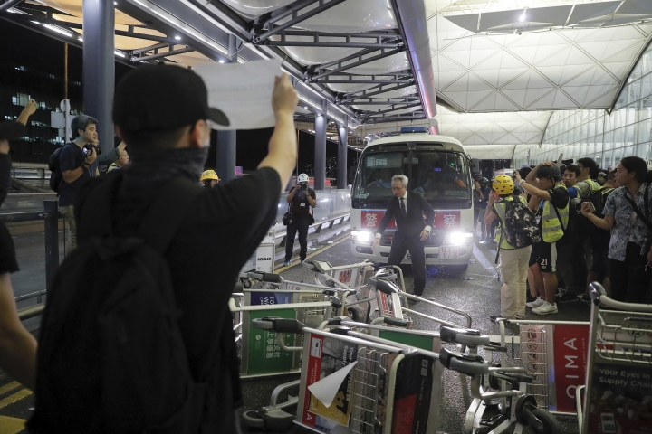 Protesters use luggage trolleys to block a police van during a demonstration at the Airport in Hong Kong, Tuesday, Aug. 13, 2019. Chaos has broken out at Hong Kong's airport as riot police moved into the terminal to confront protesters who shut down operations at the busy transport hub for two straight days. (AP Photo/Kin Cheung)