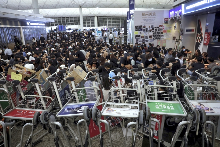 Protesters use luggage trolleys to block the walkway to the departure gates during a demonstration at the Airport in Hong Kong, Tuesday, Aug. 13, 2019. Protesters severely crippled operations at Hong Kong's international airport for a second day Tuesday, forcing authorities to cancel all remaining flights out of the city after demonstrators took over the terminals as part of their push for democratic reforms.(AP Photo/Vincent Yu)
