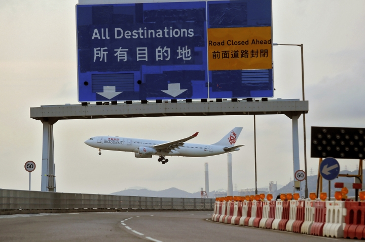 A Dragonair plane flies past a road sign at the airport in Hong Kong, Tuesday, Aug. 13, 2019. Protesters severely crippled operations at Hong Kong's international airport for a second day Tuesday, forcing authorities to cancel all remaining flights out of the city after demonstrators took over the terminals as part of their push for democratic reforms. (AP Photo/Kin Cheung)