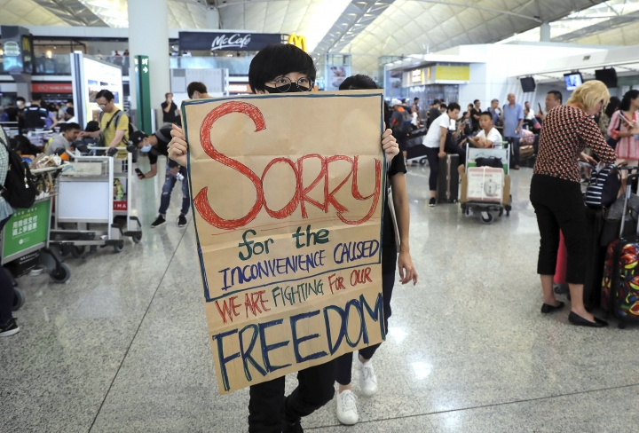 A protester shows a placard to stranded travelers during a demonstration at the Airport in Hong Kong, Tuesday, Aug. 13, 2019. Protesters severely crippled operations at Hong Kong's international airport for a second day Tuesday, forcing authorities to cancel all remaining flights out of the city after demonstrators took over the terminals as part of their push for democratic reforms. (AP Photo/Kin Cheung)