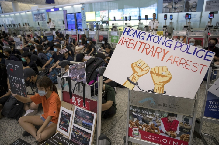 Protesters stage a sit-in rally at the departure gates of the Hong Kong International Airport in Hong Kong, Tuesday, Aug. 13, 2019. Protesters severely crippled operations at Hong Kong's international airport for a second day Tuesday, forcing authorities to cancel all remaining flights out of the city after demonstrators took over the terminals as part of their push for democratic reforms. (AP Photo/Vincent Thian)