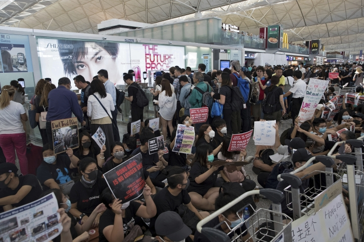 Travelers walk past as protesters hold a sit-in rally near the departure gate of the Hong Kong International Airport in Hong Kong, Tuesday, Aug. 13, 2019. Protesters clogged the departure area at Hong Kong's reopened airport Tuesday, a day after they forced one of the world's busiest transport hubs to shut down entirely amid their calls for an independent inquiry into alleged police abuse. (AP Photo/Vincent Thian)