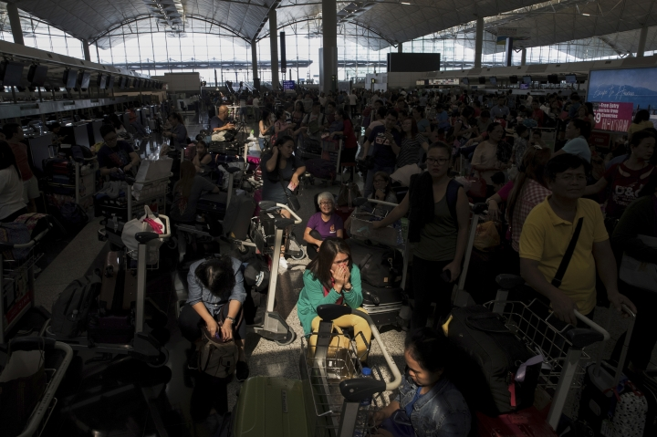 A beam of sunlight is cast on the travelers as they wait at the check-in counters in the departure hall of the Hong Kong International Airport in Hong Kong, Tuesday, Aug. 13, 2019. Protesters clogged the departure area at Hong Kong's reopened airport Tuesday, a day after they forced one of the world's busiest transport hubs to shut down entirely amid their calls for an independent inquiry into alleged police abuse. (AP Photo/Vincent Thian)