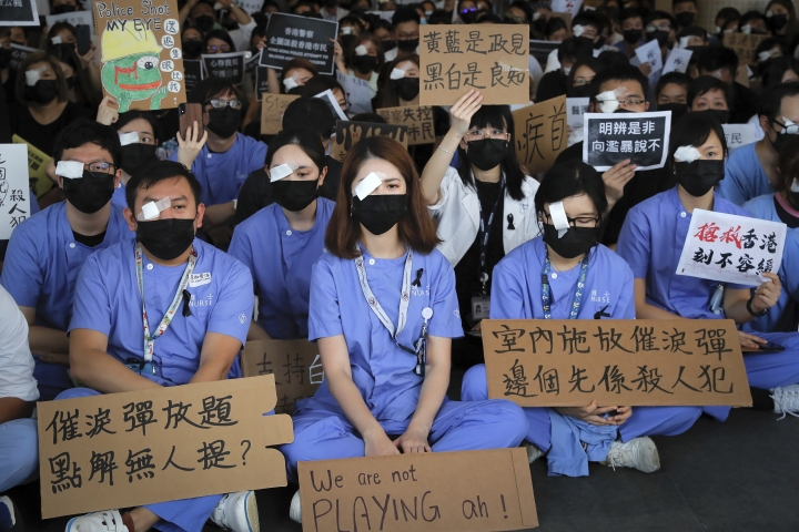 """Medical staff stage a protest against police brutality on the protesters, at a hospital in Hong Kong, Tuesday, Aug. 13, 2019. Demonstrators have in recent days focused on their demand for an independent inquiry into what they call the police's abuse of power and negligence. That followed reports and circulating video footage of violent arrests and injuries sustained by protesters. The signs read """"Why no one mentions about tear gas?,"""" bottom left and """"Using tear gas at indoor, who is the actual murderer,"""" bottom right. (AP Photo/Kin Cheung)"""