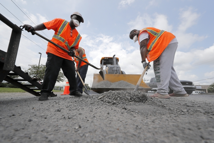Construction workers from the Louisiana Department of Transportation and Development work in the heat on a road grating project on Airline Highway in St. Rose, La., Tuesday, Aug. 13, 2019. Forecasters say most of the South, from Texas to parts of South Carolina, will be under heat advisories and warnings as temperatures will feel as high as 117 degrees. (AP Photo/Gerald Herbert)