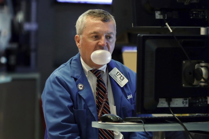 Trader James Lamb watches his screens as he works on the floor of the New York Stock Exchange, Monday, Aug. 12, 2019. Stocks are extending their losses at midday as investors opened the week heading for safety amid heightened anxiety over the U.S.-China trade war. (AP Photo/Richard Drew)