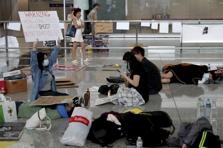 A protester shows a placard to travellers as they continue their sit-in rally at the airport in Hong Kong, Wednesday, Aug. 14, 2019. Flight operations resumed at the airport Wednesday morning after two days of disruptions marked by outbursts of violence highlighting the hardening positions of pro-democracy protesters and the authorities in the Chinese city that's a major international travel hub. (AP Photo/Vincent Thian)