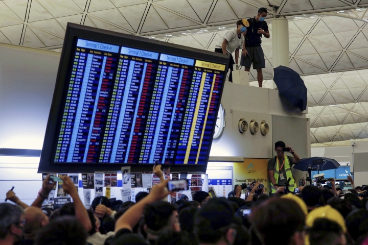 Protester use an umbrellas to block surveillance cameras during a demonstration at the Airport in Hong Kong, Tuesday, Aug. 13, 2019. Riot police clashed with pro-democracy protesters at Hong Kong's airport late Tuesday night, a chaotic end to a second day of demonstrations that caused mass flight cancellations at the Chinese city's busy transport hub. (AP Photo/Vincent Yu)