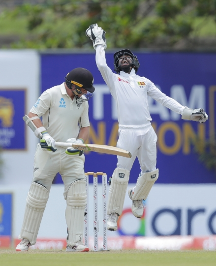 Sri Lankan wicketkeeper Niroshan Dickwella, right, celebrates taking a catch to dismiss New Zealand's Tom Latham during the day one of the first test cricket match between Sri Lanka and New Zealand in Galle, Sri Lanka, Wednesday, Aug. 14, 2019. (AP Photo/Eranga Jayawardena)