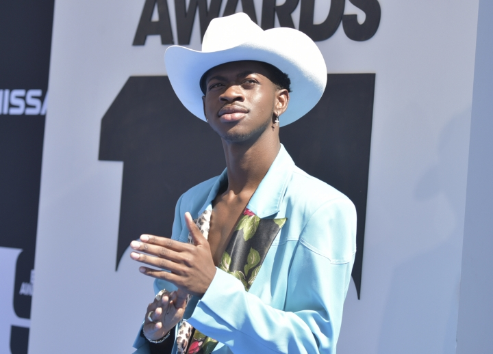 "FILE - In this June 23, 2019 file photo, Lil Nas X arrives at the BET Awards at the Microsoft Theater in Los Angeles. Lil Nas X created a musical phenomenon with his song ""Old Town Road"" with Billy Ray Cyrus, but many in Nashville are trying to decide whether to nominate it for a country music award. Voting is under way now for nominations for the Country Music Association Awards, held on Nov. 13, but the song faces an uphill challenge. (Photo by Richard Shotwell/Invision/AP, File)"