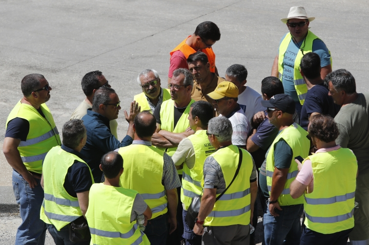 Tanker truck drivers on strike gather to listen to a workers union spokesman outside a fuel depot in Aveiras, outside Lisbon, Tuesday, Aug. 13, 2019. Soldiers and police officers are driving tanker trucks to distribute gas in Portugal as an open-ended truckers' strike over pay enters its second day. The government has issued an order allowing the army to be used. (AP Photo/Armando Franca)