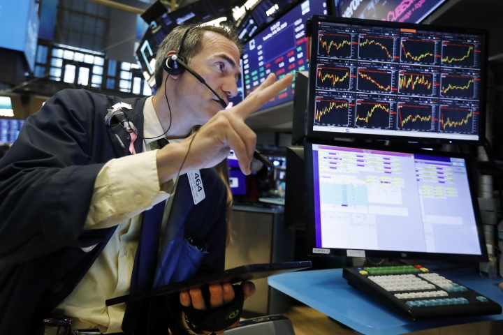 FILE - In this July 30, 2019 file photo, trader Gregory Rowe works on the floor of the New York Stock Exchange. An economic alarm bell is sounding in the U.S. and sending warnings of a potential recession. Yields on 2-year and 10-year Treasury notes inverted early Wednesday, Aug. 14, a market phenomenon that shows investors want more in return for short-term government bonds than they are for long-term bonds. (AP Photo/Richard Drew)
