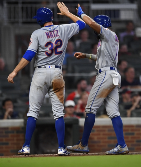 New York Mets' Steven Matz (32) and Amed Rosario congratulate each other at home plate after scoring on a J.D. Davis single during the seventh inning of the team's baseball game against the Atlanta Braves, Wednesday, Aug.14, 2019, in Atlanta. (AP Photo/John Amis)