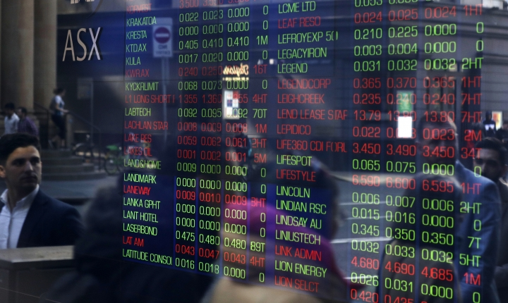 People are reflected in a window as they walk past the Australian Stock Exchange in Sydney, Thursday, Aug. 15, 2019. Asian stock markets followed Wall Street lower on Thursday after the Dow Jones Industrial Average plunged on mounting fears of a possible recession. (AP Photo/Rick Rycroft)