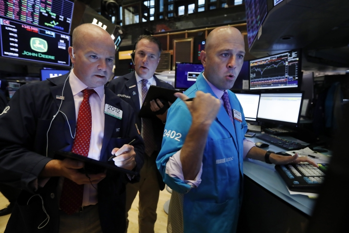 Traders Patrick Casey, left, and Jonathan Corpina, center, work with specialist Jay Woods on the floor of the New York Stock Exchange, Wednesday, Aug. 14, 2019. The Dow Jones Industrial Average sank 800 points after the bond market flashed a warning sign about a possible recession for the first time since 2007. (AP Photo/Richard Drew)