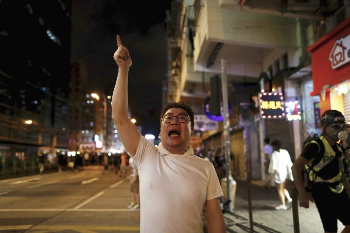 A man shouts at policemen as protesters face off with policemen in Hong Kong, Wednesday, Aug. 14, 2019. German Chancellor Angela Merkel is calling for a peaceful solution to the unrest in Hong Kong amid fears China could use force to quell pro-democracy protests. (AP Photo/Vincent Yu)