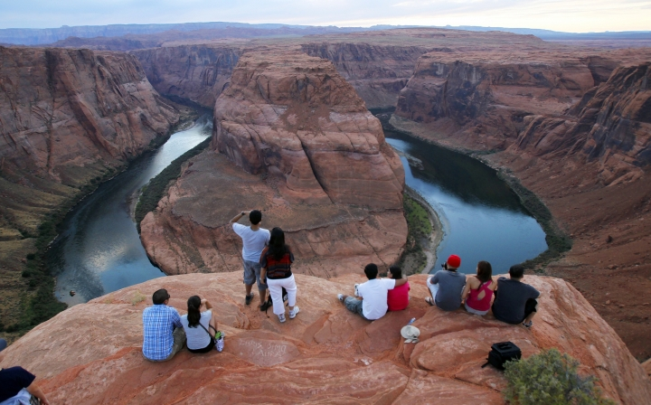 FILE - In this Sept. 9, 2011 file photo visitors view the dramatic bend in the Colorado River at the popular Horseshoe Bend in Glen Canyon National Recreation Area, in Page, Ariz. Some 40 million people in Arizona, California, Colorado, Nevada, New Mexico, Utah and Wyoming draw from the Colorado River and its tributaries. Much of that originates as snow. A wet winter likely will fend off mandated water shortages for states in the U.S. West that rely on the river but won't erase the impact of climate change. Climate change means the region is still getting drier and hotter. (AP Photo/Ross D. Franklin, File)