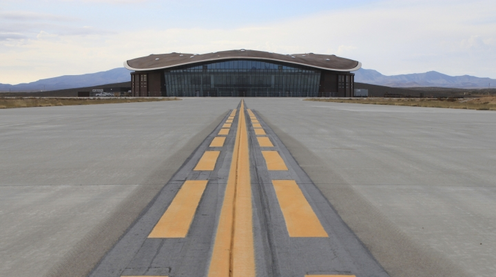 FILE - This Dec. 9, 2014 photo shows the taxiway leading to the hangar at Spaceport America in Upham, N.M. Virgin Galactic is scheduled to unveil the interior of its digs at Spaceport America, providing the first glimpse of mission control, a prep area for pilots and where paying customers will lounge ahead of their suborbital flights. Company officials are gathering Thursday, Aug. 15, 2019, at the remote facility in the New Mexico desert to show off two levels of the custom-tailored hangar at the taxpayer-financed spaceport. (AP Photo/Susan Montoya Bryan, File)